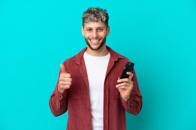 Giovane uomo caucasico bello isolato su sfondo blu usando il telefono cellulare mentre fa i pollici in su