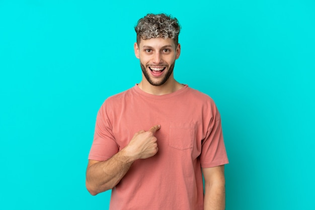 Giovane uomo caucasico bello isolato su sfondo blu con espressione facciale a sorpresa