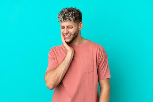 Giovane uomo caucasico bello isolato su sfondo blu con mal di denti