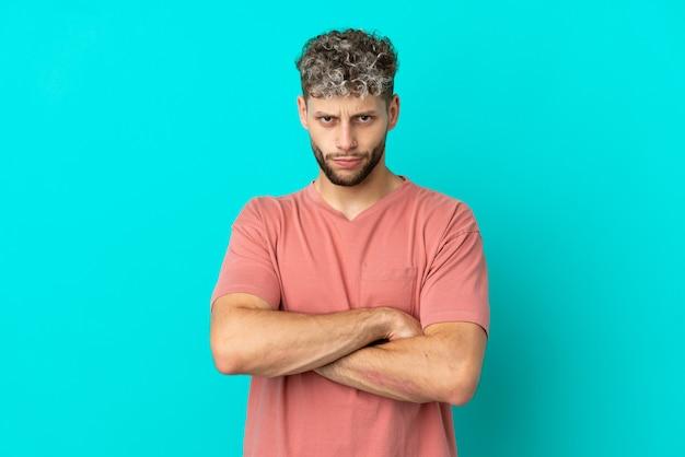Giovane uomo caucasico bello isolato su sfondo blu con espressione infelice