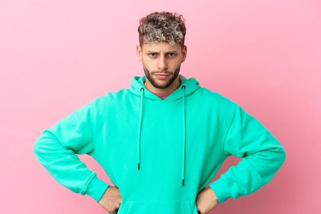 Giovane uomo caucasico bello isolato su sfondo rosa arrabbiato