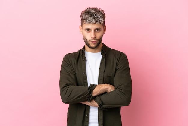 Giovane uomo caucasico bello isolato su sfondo rosa sentirsi sconvolto