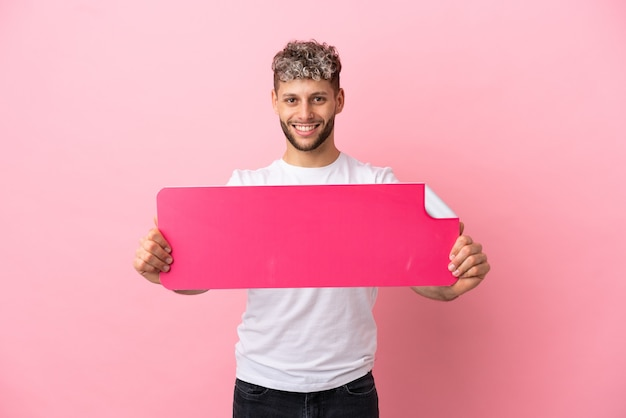 Giovane uomo caucasico bello isolato su sfondo rosa con in mano un cartello vuoto