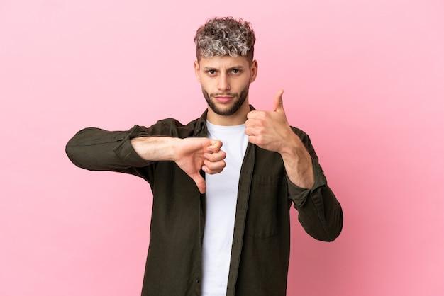 Giovane uomo caucasico bello isolato su sfondo rosa facendo segno buono-cattivo. indeciso tra si o no