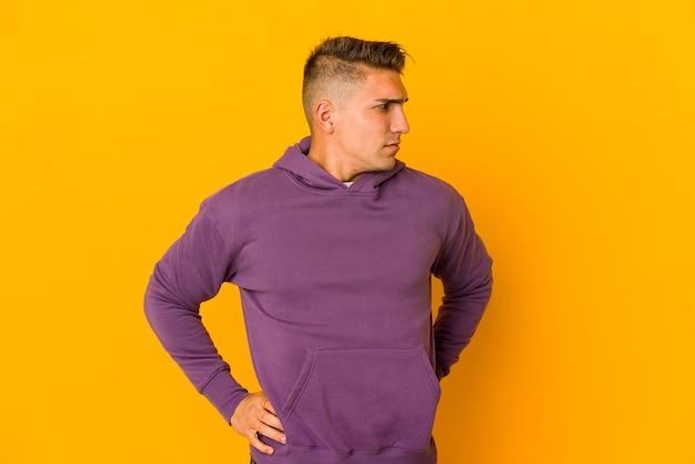 Giovane uomo caucasico bello isolato che soffre di mal di schiena.