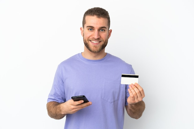 Giovane uomo caucasico bello isolato su sfondo bianco che acquista con il cellulare con una carta di credito