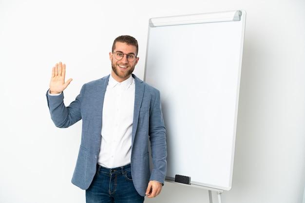 Giovane uomo caucasico bello isolato su bianco che dà una presentazione sulla lavagna bianca e saluta con la mano