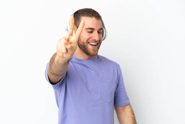 Giovane uomo caucasico bello isolato sulla parete bianca che ascolta musica e canto
