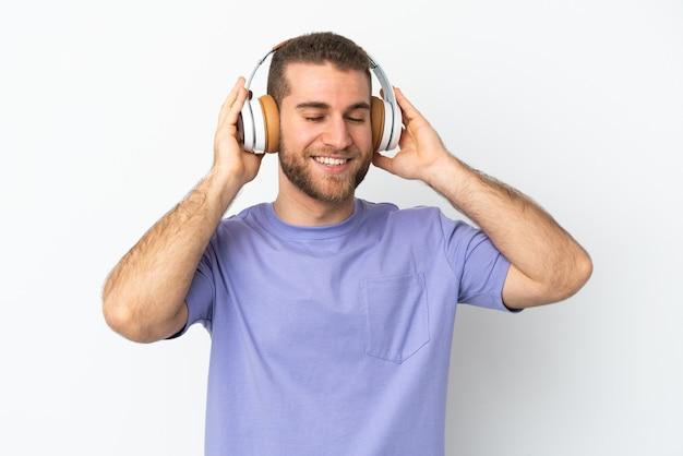Giovane uomo caucasico bello isolato sulla musica d'ascolto della parete bianca