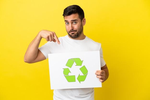 Giovane uomo caucasico bello isolato su sfondo giallo che tiene un cartello con l'icona di riciclo e lo punta