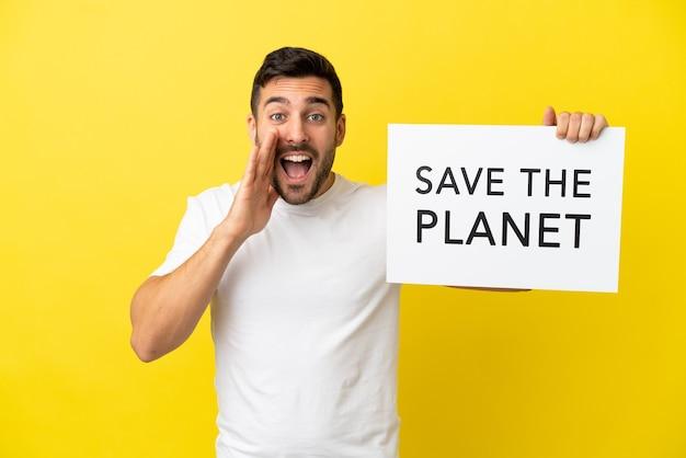 Giovane uomo caucasico bello isolato su sfondo giallo che tiene un cartello con il testo salva il pianeta e urla