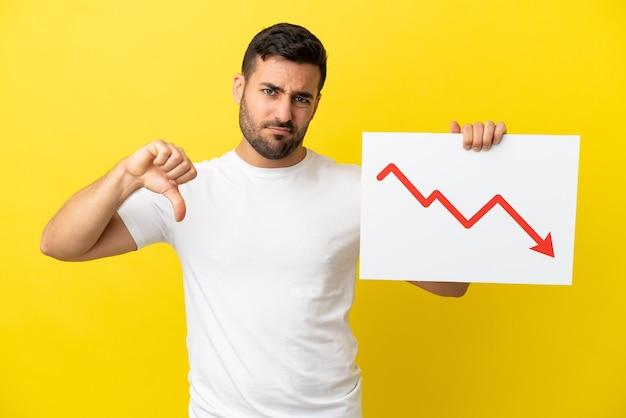 Giovane uomo caucasico bello isolato su sfondo giallo che tiene un cartello con un simbolo di freccia di statistiche decrescenti e fa un cattivo segnale