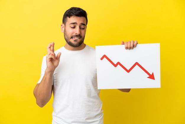 Giovane uomo caucasico bello isolato su sfondo giallo con in mano un cartello con un simbolo di freccia di statistiche decrescenti con le dita incrociate