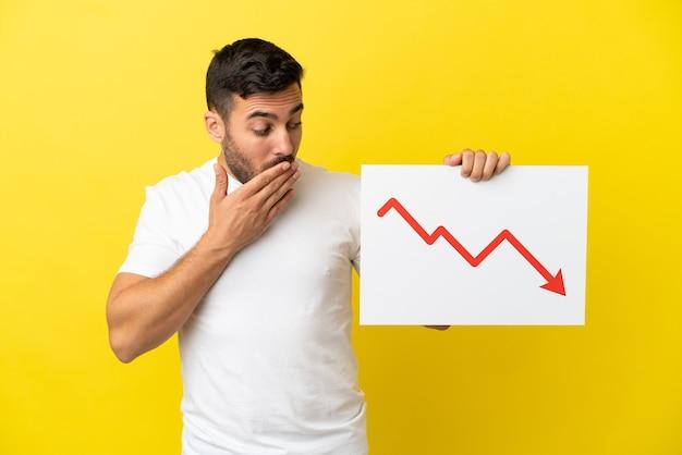 Giovane uomo caucasico bello isolato su sfondo giallo con in mano un cartello con un simbolo di freccia di statistiche decrescenti con espressione sorpresa
