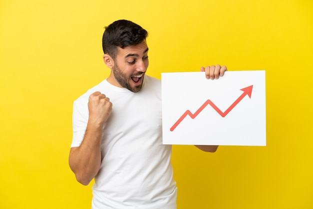 Giovane uomo caucasico bello isolato su sfondo giallo con in mano un cartello con un simbolo di freccia statistica in crescita e celebrando una vittoria