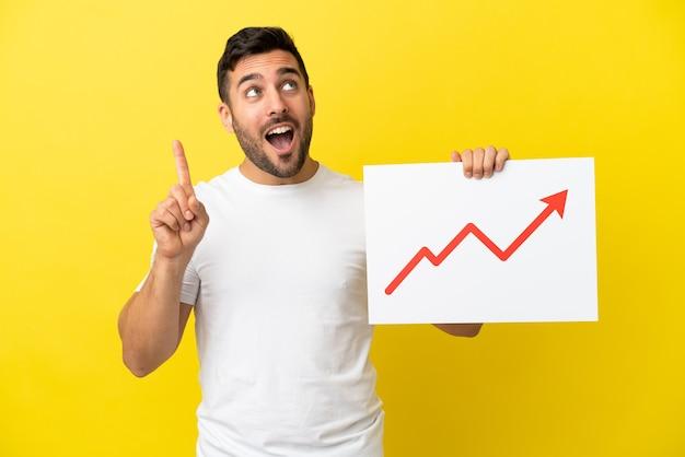 Giovane uomo caucasico bello isolato su sfondo giallo con in mano un cartello con un simbolo di freccia statistica in crescita e pensiero