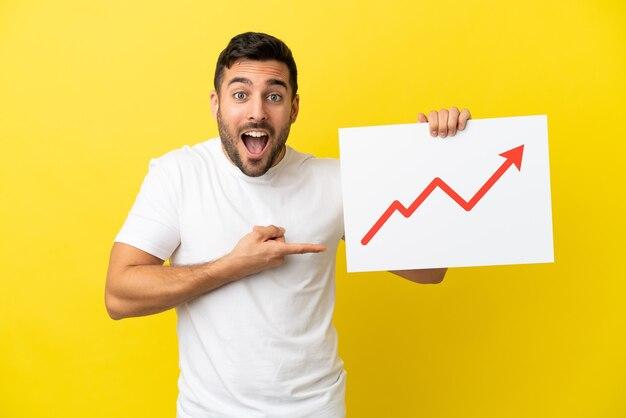 Giovane uomo caucasico bello isolato su sfondo giallo con in mano un cartello con un simbolo di freccia statistica in crescita con espressione sorpresa