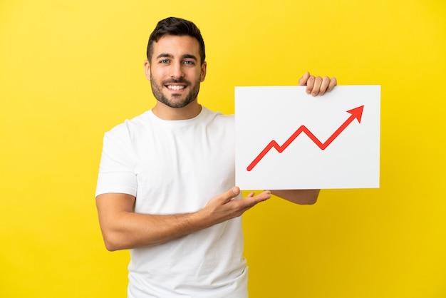 Giovane uomo caucasico bello isolato su sfondo giallo con in mano un cartello con un simbolo di freccia di statistiche in crescita