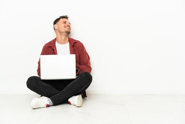 Sit-in di giovane uomo caucasico bello sul pavimento con il computer portatile felice e sorridente