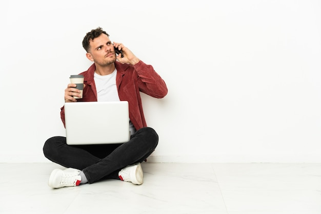Sit-in di giovane uomo caucasico bello sul pavimento con il computer portatile che tiene il caffè da portare via e un cellulare