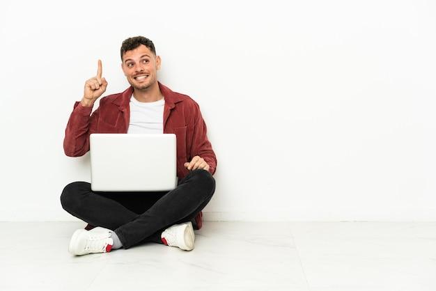 Il giovane uomo caucasico bello sit-in sul pavimento con il computer portatile che intende realizzare la soluzione mentre solleva un dito