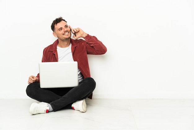 Giovane uomo caucasico bello sit-in sul pavimento con il computer portatile mantenendo una conversazione con il telefono cellulare