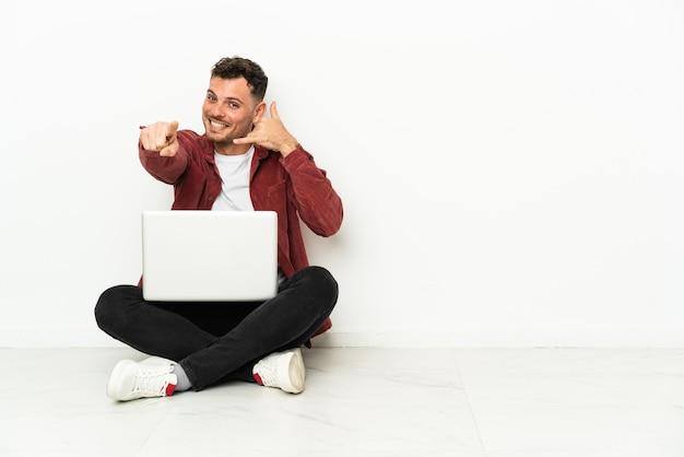 Giovane uomo caucasico bello sit-in sul pavimento con il computer portatile che fa il gesto del telefono