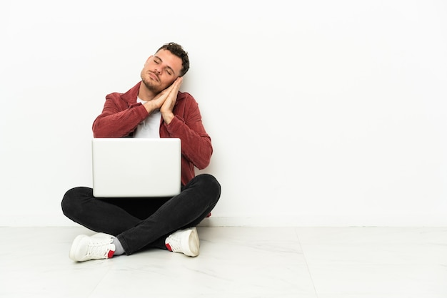 Sit-in di giovane uomo caucasico bello sul pavimento con il computer portatile che fa gesto di sonno nell'espressione dorable