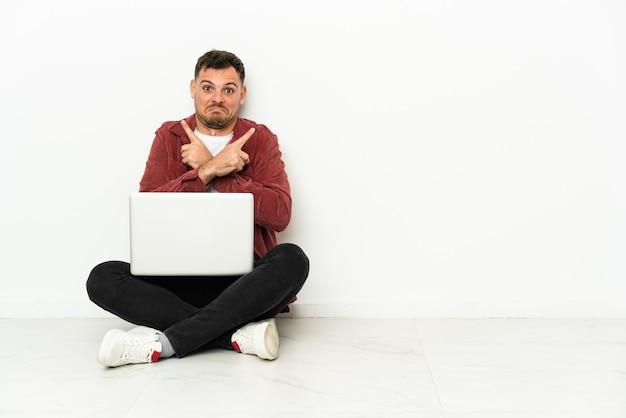 Sit-in di giovane uomo caucasico bello sul pavimento con il computer portatile che indica i laterals che hanno dubbi