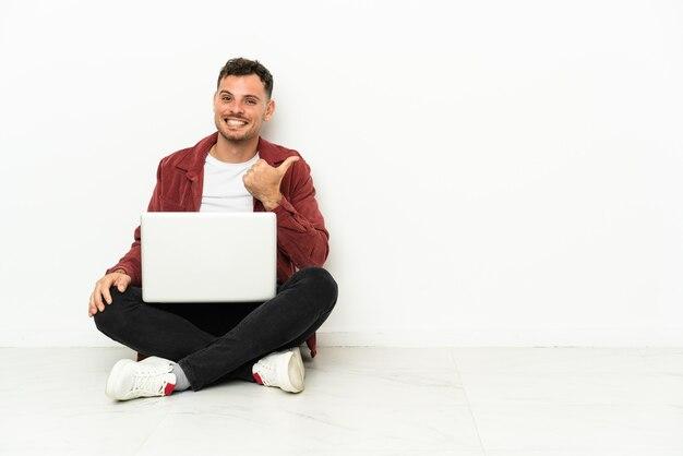 Sit-in del giovane uomo caucasico bello sul pavimento con il computer portatile che indica al lato per presentare un prodotto