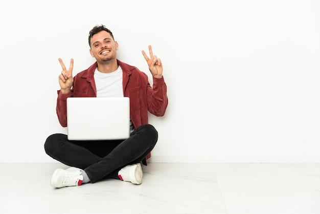 Giovane uomo caucasico bello sit-in sul pavimento con il computer portatile che mostra il segno di vittoria con entrambe le mani