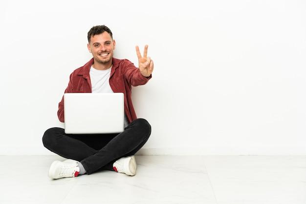 Sit-in di giovane uomo caucasico bello sul pavimento con il computer portatile che sorride e che mostra il segno di vittoria