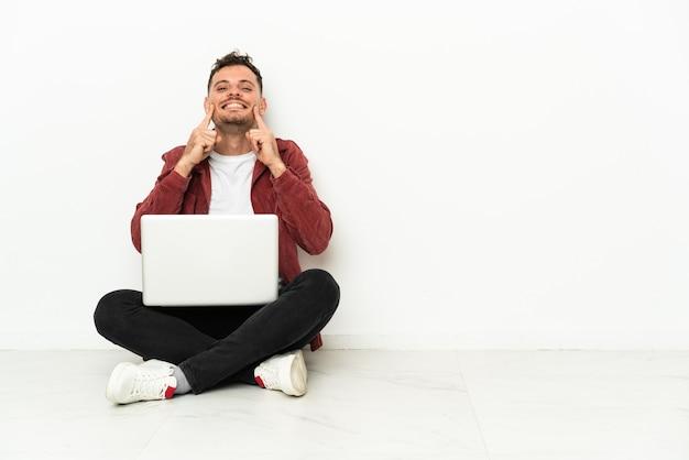 Sit-in di giovane uomo caucasico bello sul pavimento con il computer portatile che sorride con un'espressione felice e piacevole