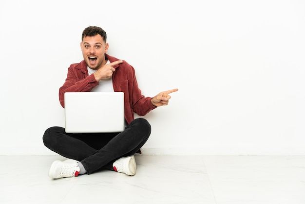 Sit-in di giovane uomo caucasico bello sul pavimento con il computer portatile sorpreso e indicando il lato