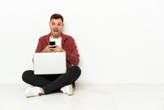 Giovane bell'uomo caucasico seduto sul pavimento con un laptop sorpreso e inviando un messaggio