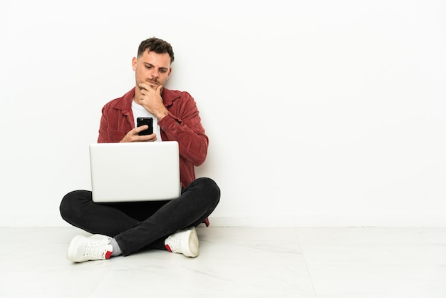 Sit-in di giovane uomo caucasico bello sul pavimento con il pensiero del computer portatile e l'invio di un messaggio