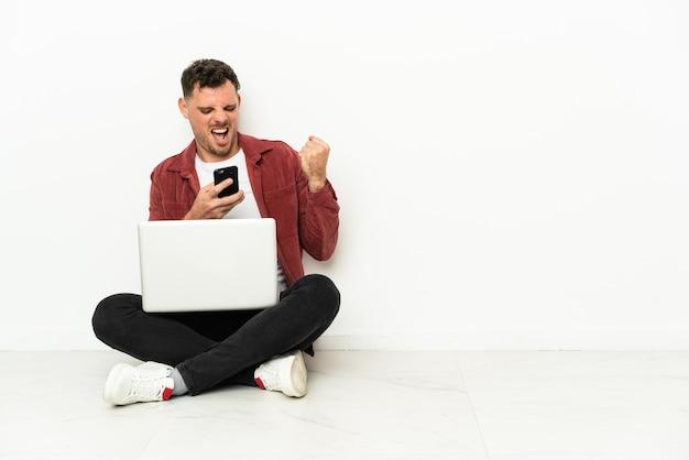 Giovane uomo caucasico bello sit-in sul pavimento con il computer portatile con il telefono in posizione di vittoria