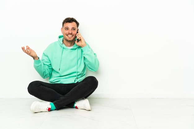 Giovane uomo caucasico bello seduto sul pavimento mantenendo una conversazione con il telefono cellulare con qualcuno