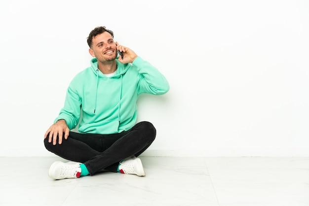 Giovane uomo caucasico bello seduto sul pavimento mantenendo una conversazione con il telefono cellulare
