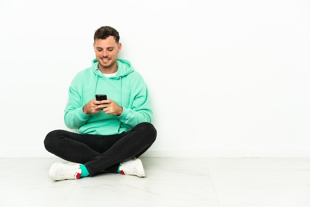 Giovane uomo caucasico bello seduto sul pavimento inviando un messaggio con il cellulare