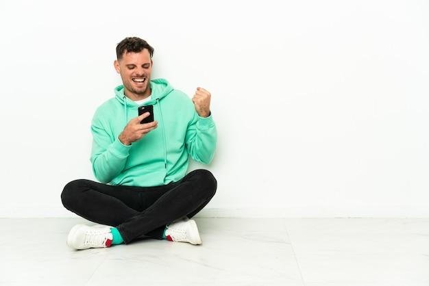 Giovane uomo caucasico bello seduto sul pavimento con il telefono in posizione di vittoria