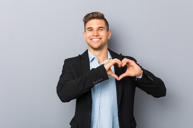 Giovane uomo caucasico bello che sorride e che mostra una forma del cuore con le mani.