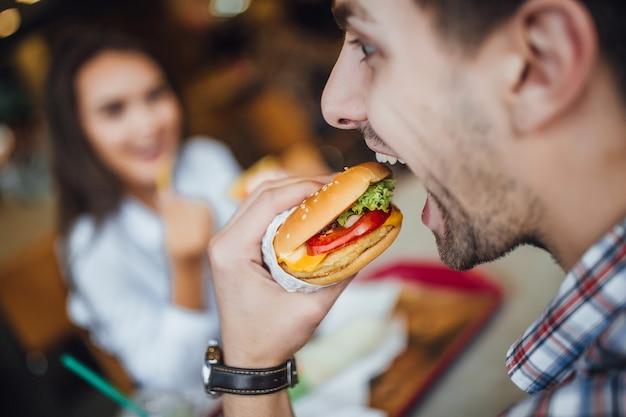 Giovane uomo caucasico bello gustoso mangiare un hamburger con formaggio sullo sfondo di una ragazza che sorride