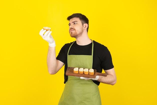 Giovane bello masticare guardando il rotolo di torta su un giallo.