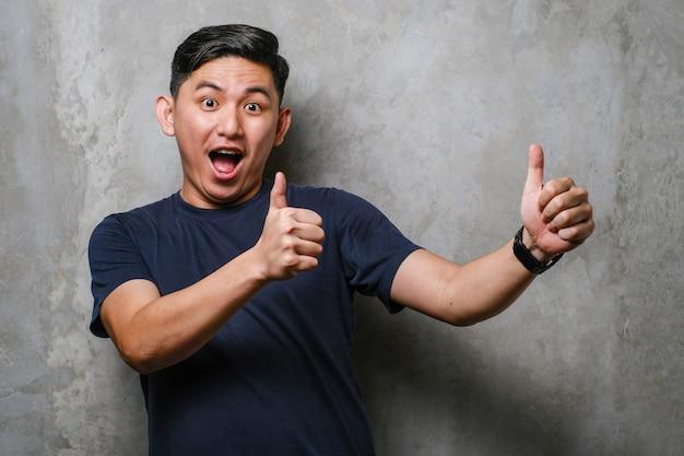 Giovane uomo cinese bello che indossa maglietta casual su sfondo muro di cemento che approva facendo gesto positivo con la mano, pollice in alto sorridente e felice per il successo. gesto vincitore.