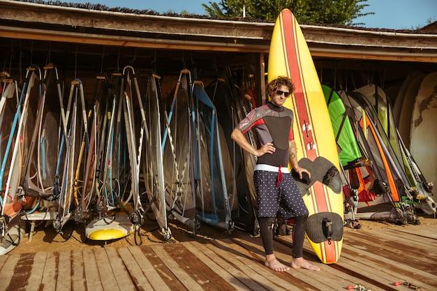 Giovane uomo riccio bello in costume da bagno e occhiali in piedi presso la capanna di surf in spiaggia