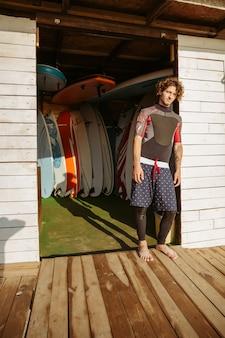 Giovane uomo riccio bello in costume da bagno in piedi presso la capanna di surf in spiaggia