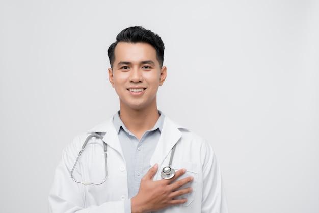 Bel giovane medico uomo che indossa uno stetoscopio su sfondo isolato sorridente con la mano sul petto con gesto grato sul viso. concetto di salute.