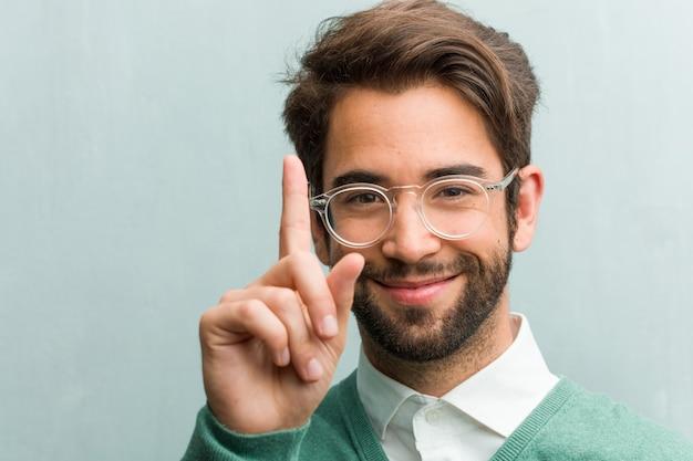 Il giovane uomo bello dell'imprenditore affronta il primo piano che mostra il numero uno, il simbolo di conteggio, il concetto di matematica, sicuro e allegro