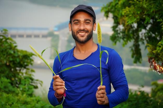 Giovane bel contadino con pianta